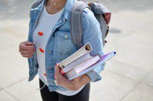 Une étudiante portant ses livres de cours